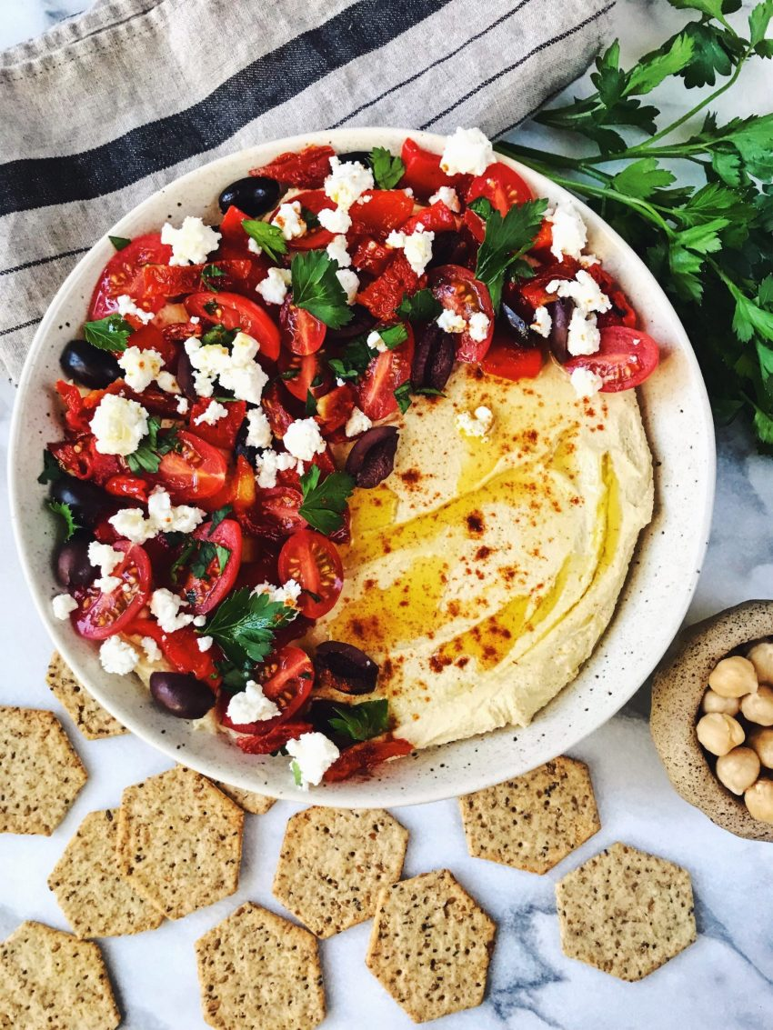 Homemade hummus with Mediterranean toppings surrounded by crackers