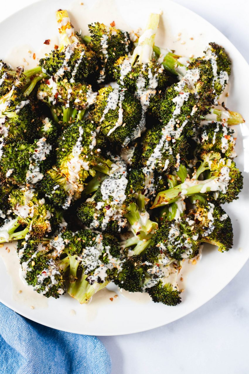 Plate of roasted broccoli drizzled with lemon tahini sauce