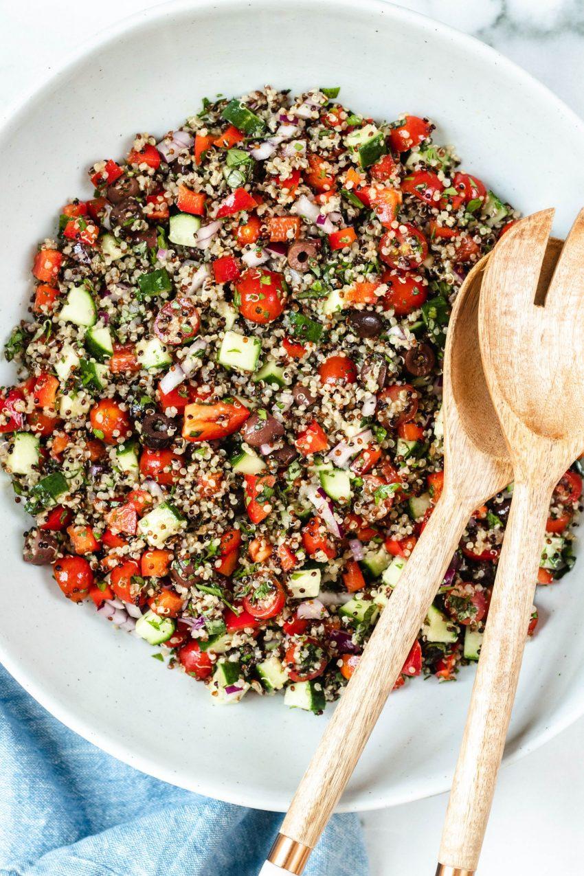Big bowl of Mediterranean quinoa salad with wooden serving spoons