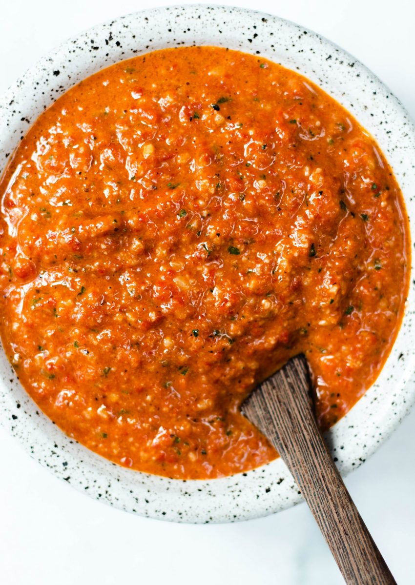 Romesco sauce in a bowl with a wooden spoon