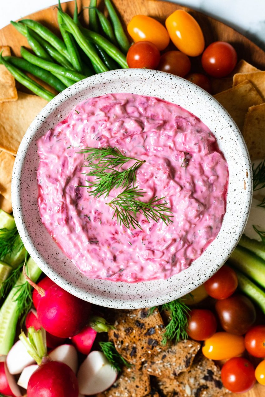 Bowl of pink beet tzatziki surrounded by vegetable crudite and crackers