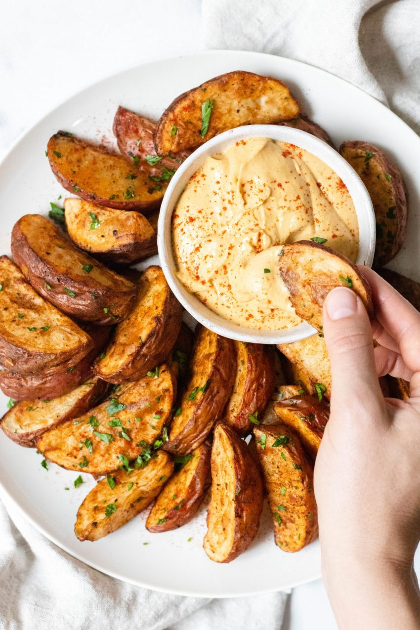 Bowl of vegan queso with roasted potato wedges with a hand dipping a potato into the queso
