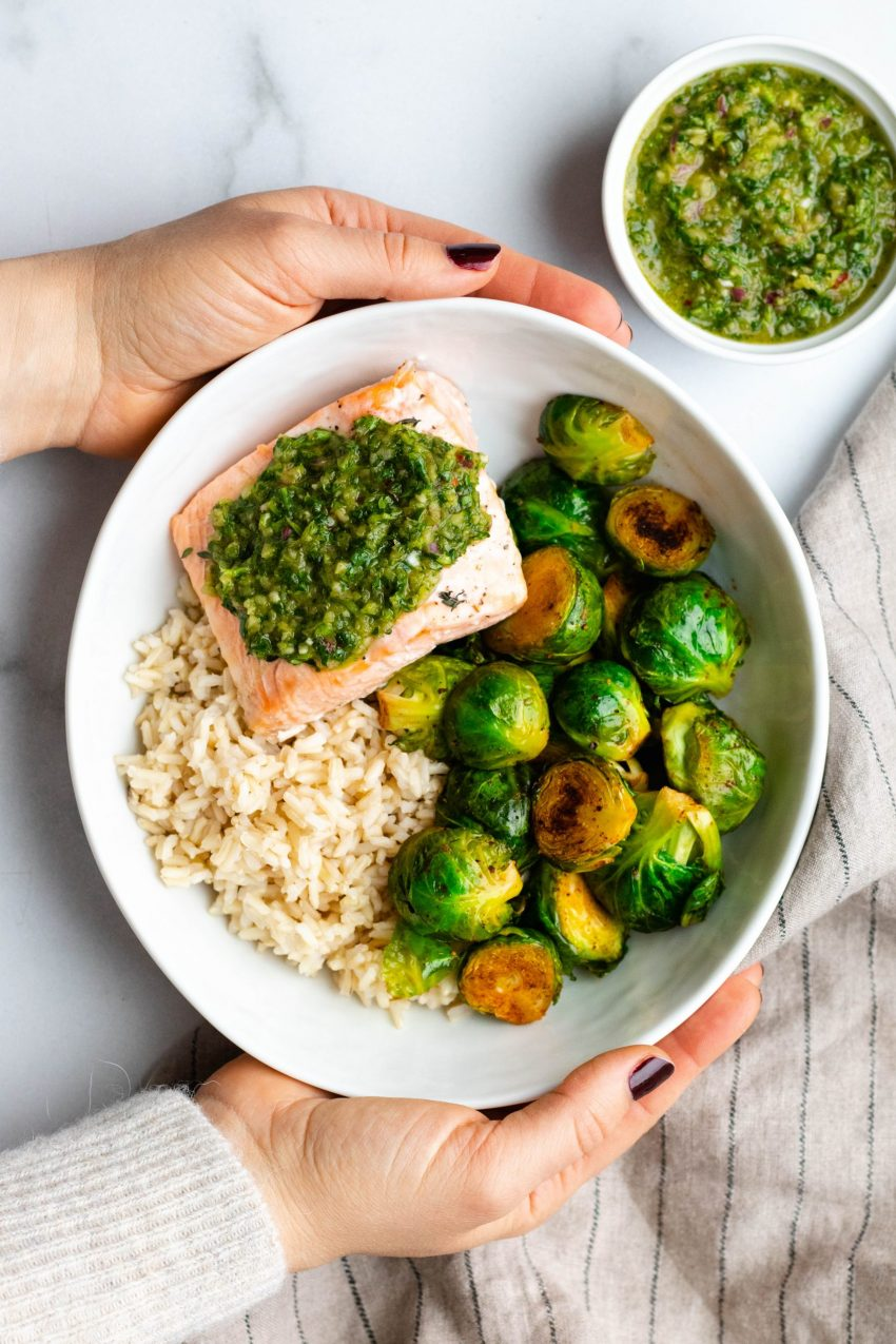 Hands holding a bowl with brown rice, brussels sprouts, and chimichurri salmon with a side of chimichurri in a dish