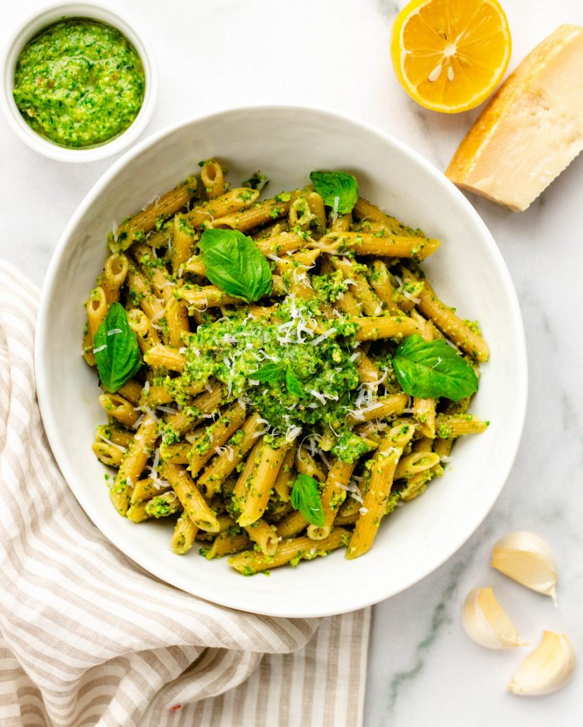 Bowl of kale pesto pasta surrounded by ingredients