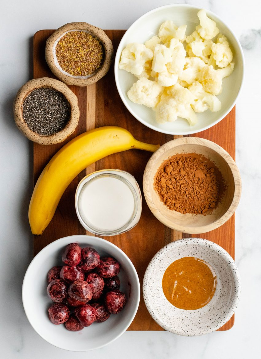 Chocolate cherry smoothie ingredients in bowls on top of a wooden cutting board