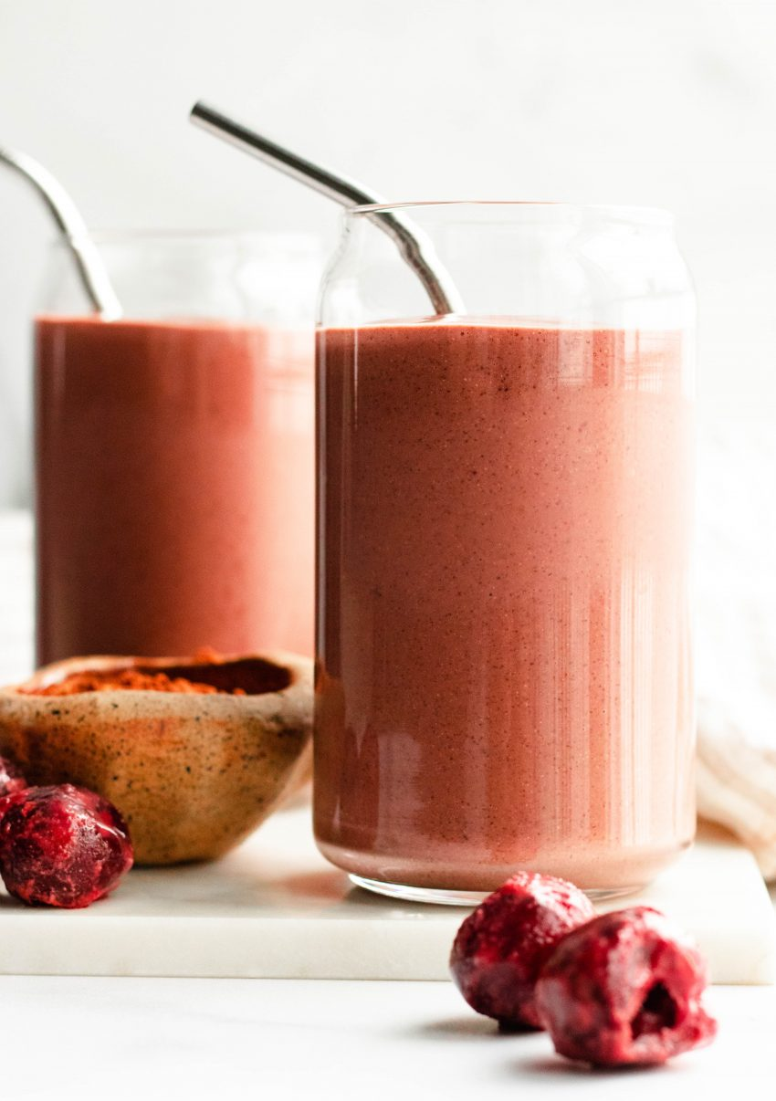 Two chocolate cherry smoothies in glasses with silver straws
