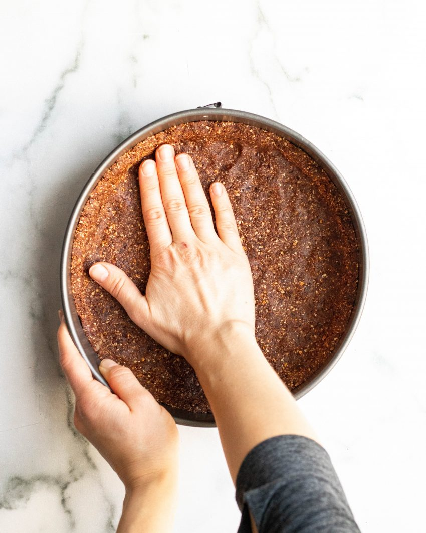 Hand pressing no bake crust into a springform pan
