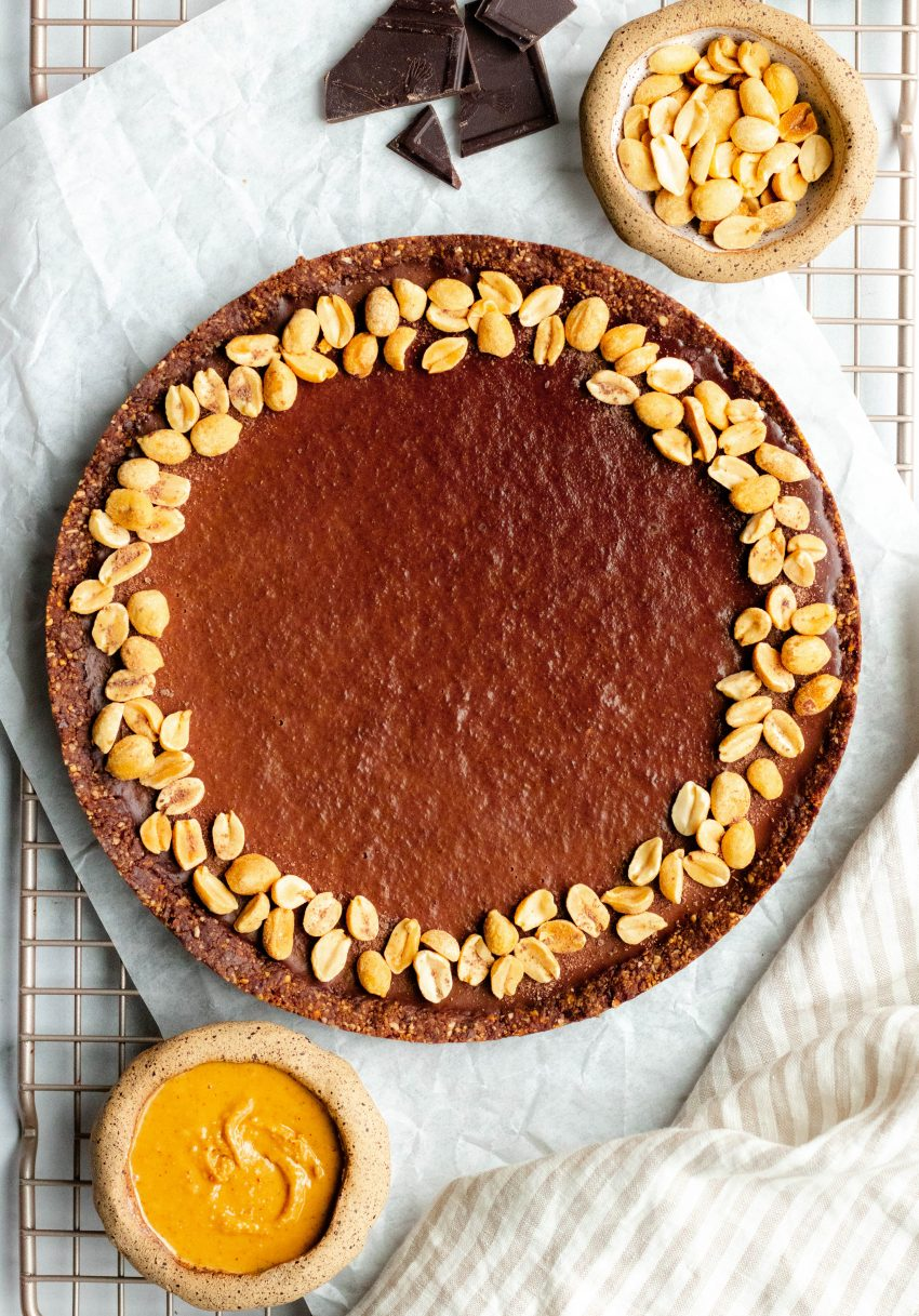 Vegan no bake chocolate peanut butter tart on parchment paper resting on wire drying rack