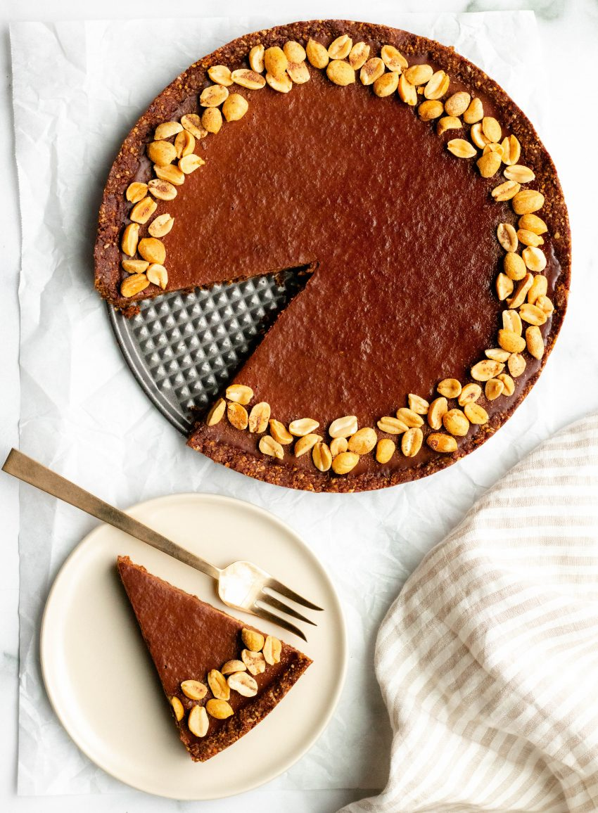 Vegan no bake chocolate peanut butter tart with one slice cut out and plated with a fork