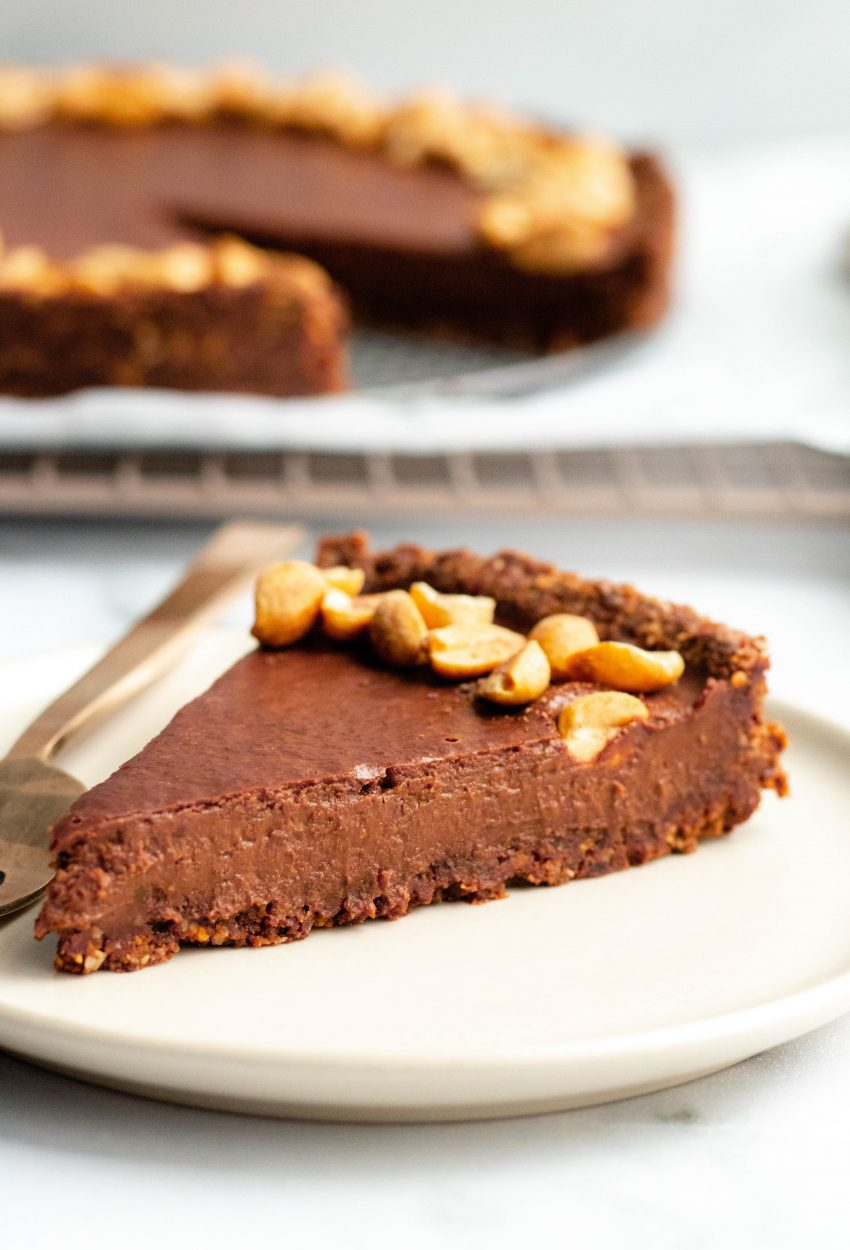 Slice of no bake chocolate peanut butter tart on a dessert plate with a gold fork