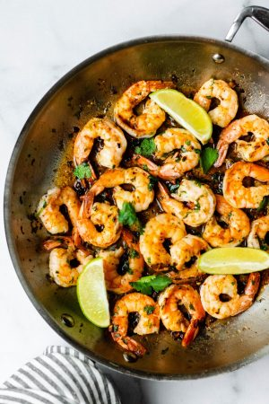 Cilantro lime shrimp in a frying pan with wedges of lime
