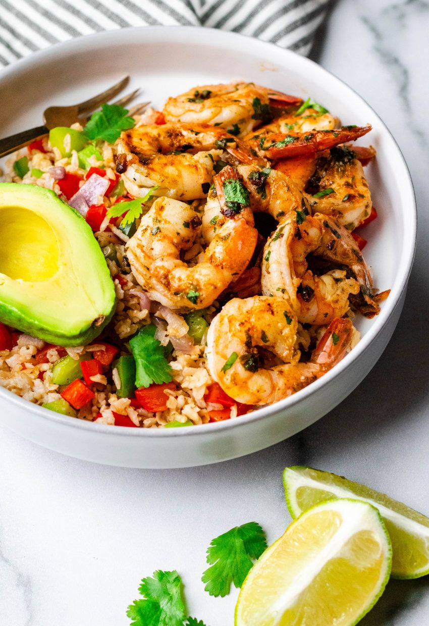 Cilantro lime shrimp in a bowl with rice, avocado and lime wedges
