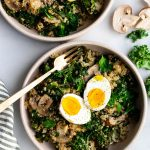 Two bowls of mushroom and kale quinoa with hard boiled eggs.