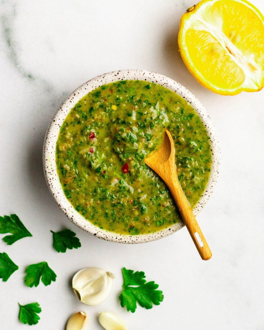 Homemade chimichurri sauce in a dish with small wooden spoon and ingredients surrounding