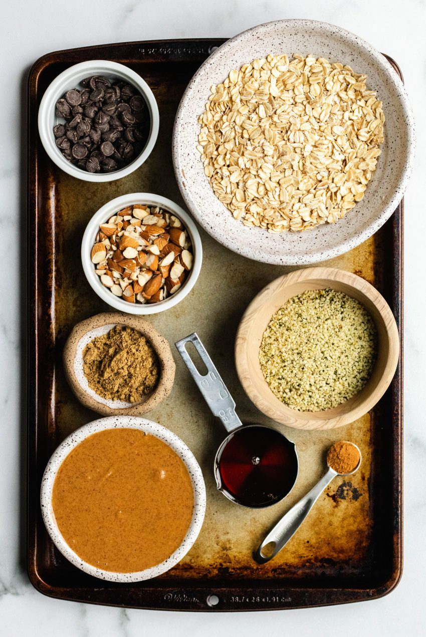 Ingredients for no bake chocolate chip almond oat bars in bowls on top of a baking sheet