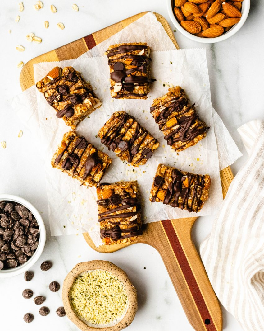 no bake chocolate chip almond oat bars on a cutting board with ramekins of ingredients surrounding
