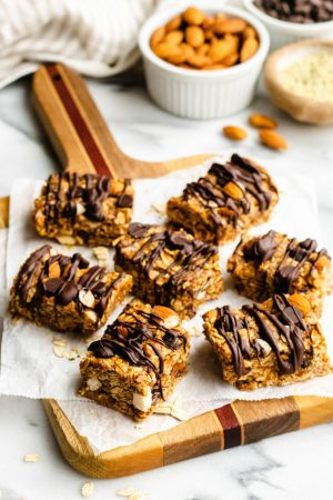 Chocolate chip almond oat bars on a cutting board with ramekins of ingredients in the background