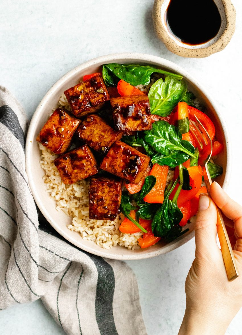 Hand holding a fork taking a bite from a bowl with honey balsamic tofu, brown rice, and sauteed vegetables