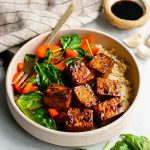Honey balsamic tofu bowl with rice and sauteed vegetables with ingredients scattered around the bowl