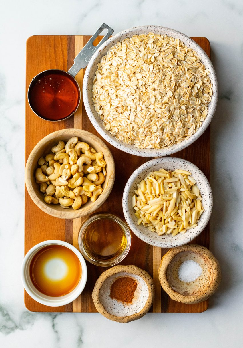 Honey nut granola ingredients in bowls on a wooden cutting board