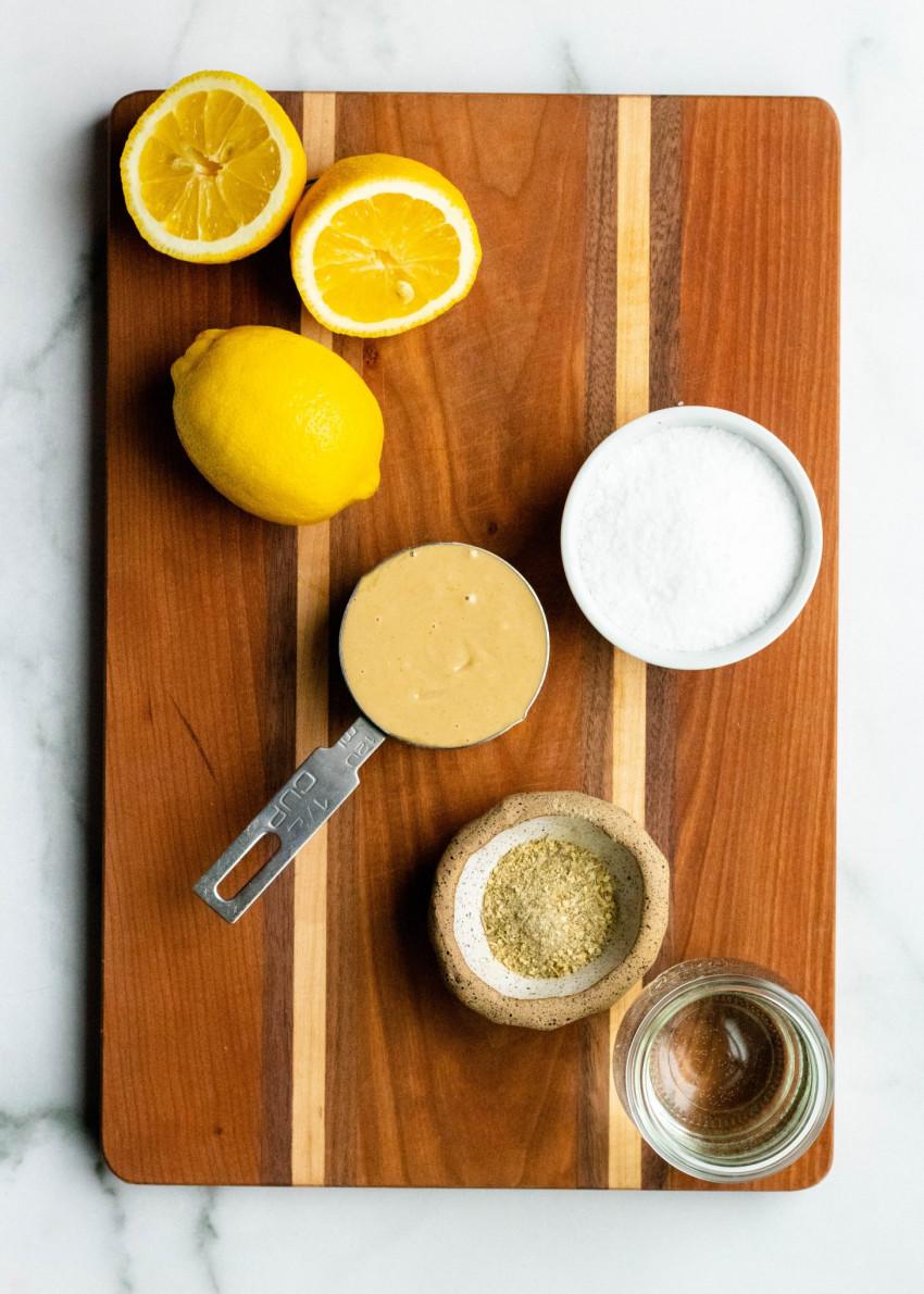 Lemon tahini sauce ingredients on a wooden cutting board