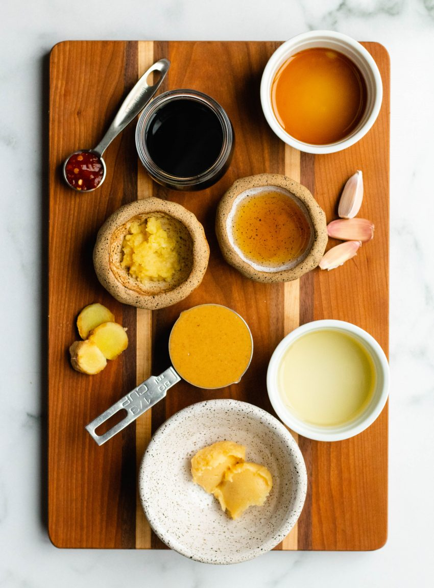 Healthy peanut sauce ingredients in bowls and measuring cups on a wooden cutting board