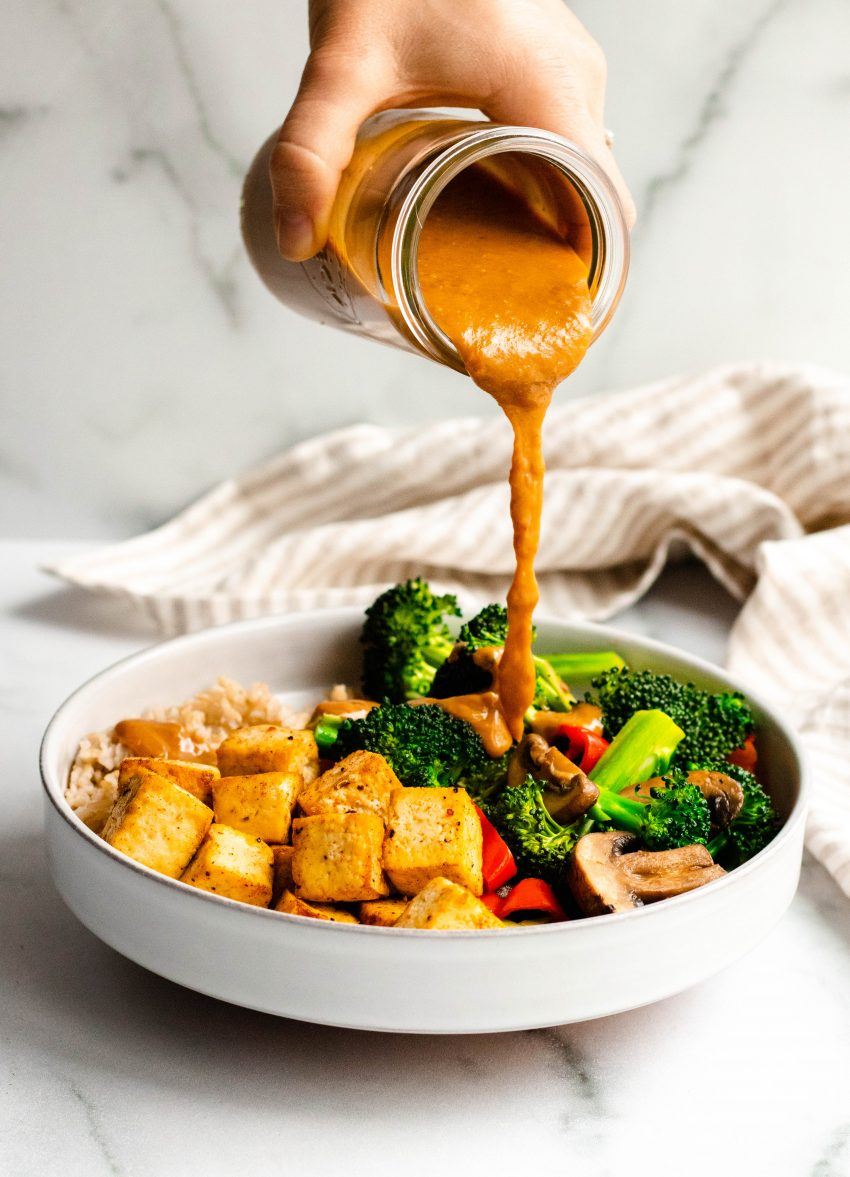 Hand pouring peanut sauce onto a bowl of rice, vegetables, and tofu