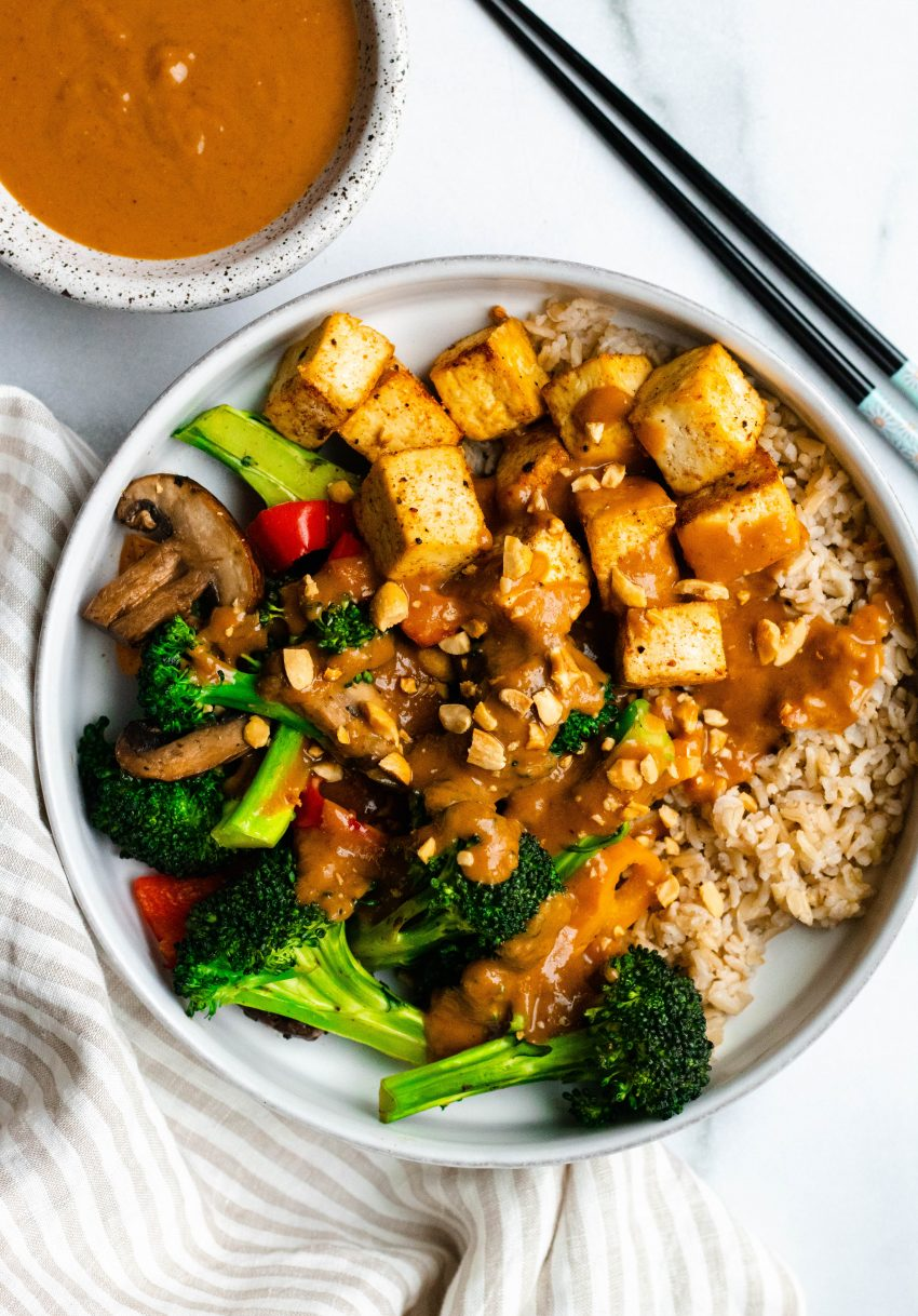 Stir fry bowl of vegetables, tofu, and brown rice with peanut sauce and chopsticks on the side