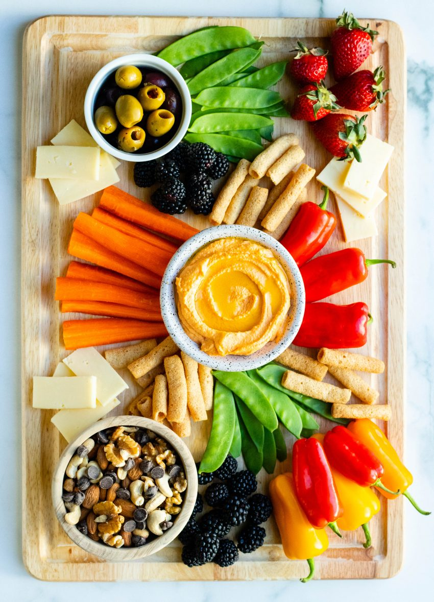 Healthy snack board with a variety of fruits, vegetables, dips, nuts, and olives