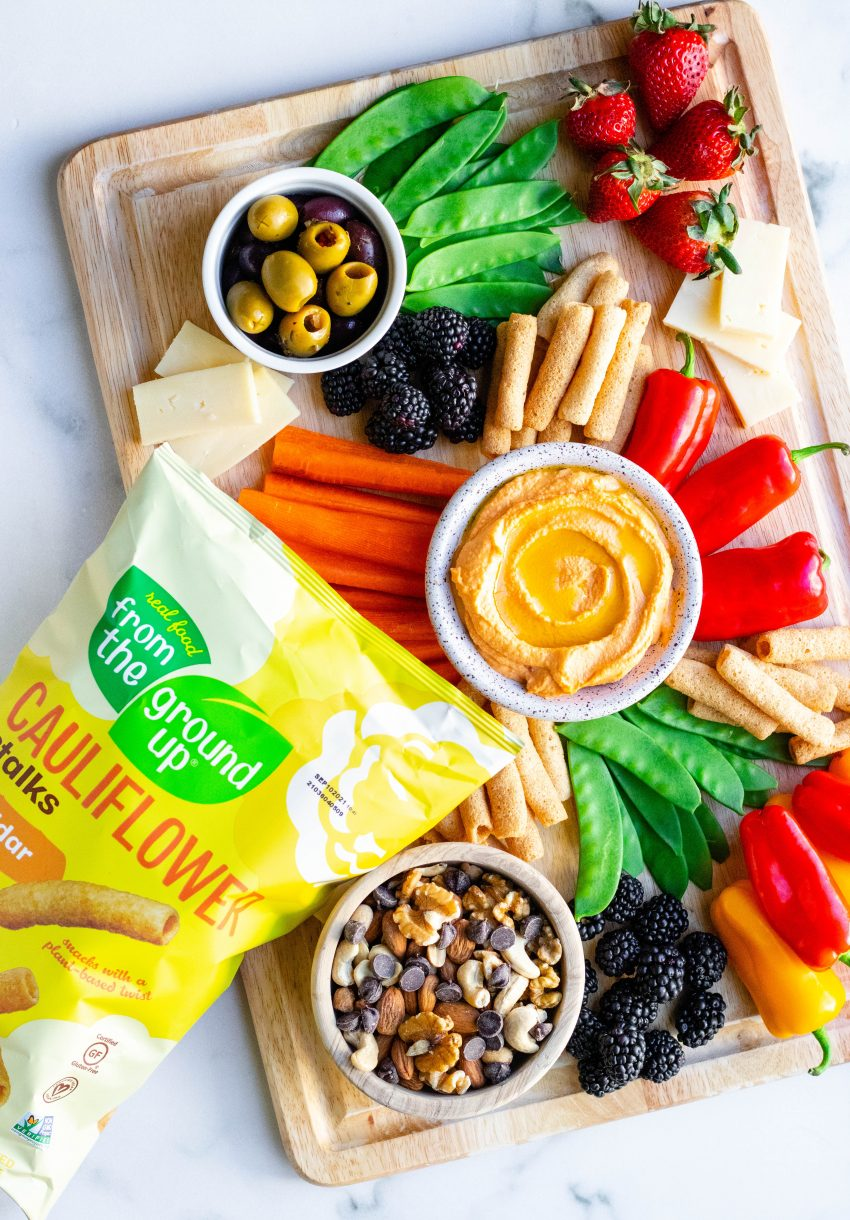 Healthy snack board with a variety of fruits, vegetables, dips, nuts, and olives with bag of cauliflower stalks