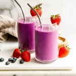 Two almond butter and jelly smoothies with metal straws on a white cutting board with berries around the glasses