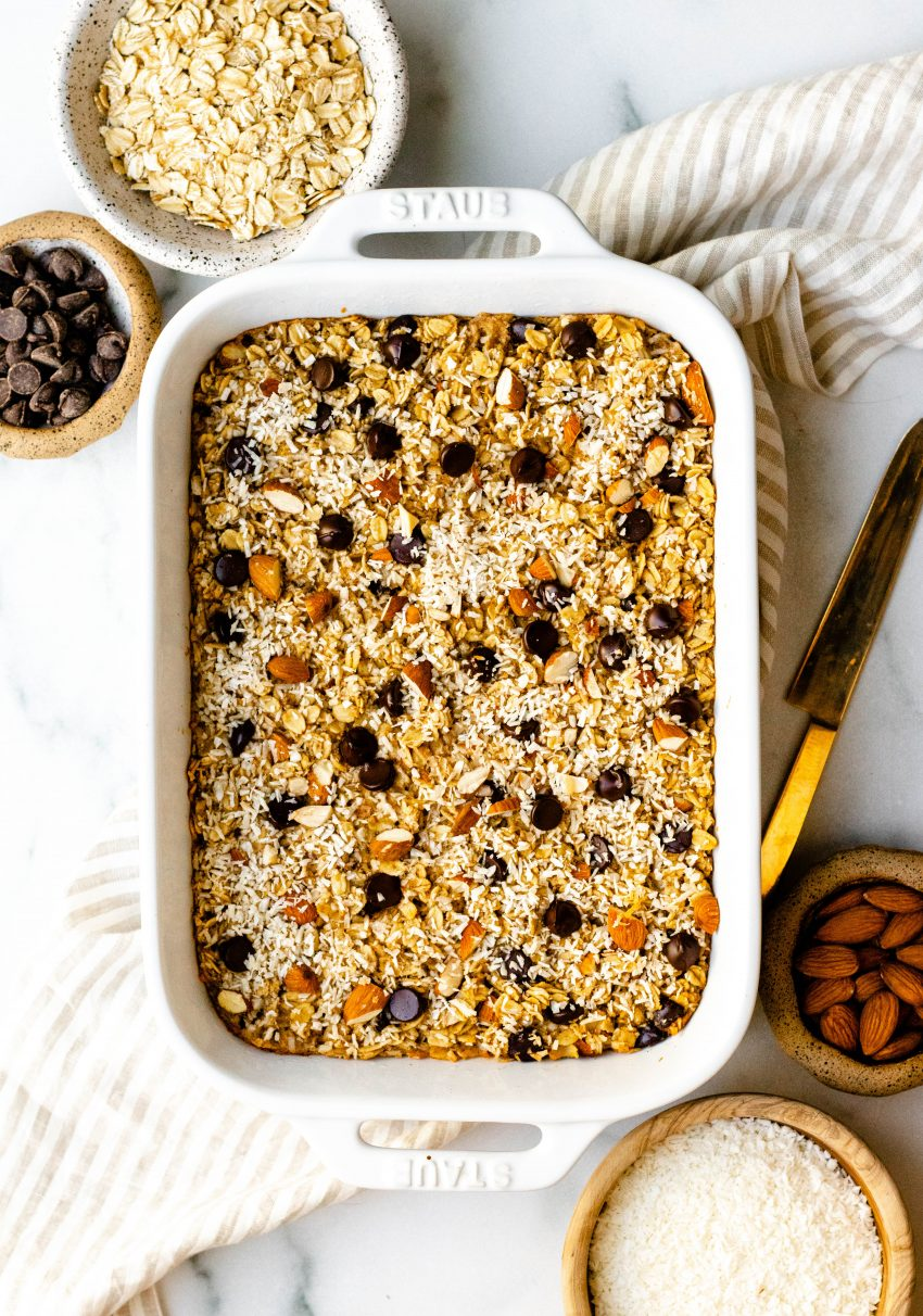 Healthy almond joy baked oatmeal squares in a white baking dish with ramekins of ingredients surrounding