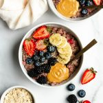 2 bowls of berry banana stovetop oatmeal with fresh berries, banana slices, and peanut butter