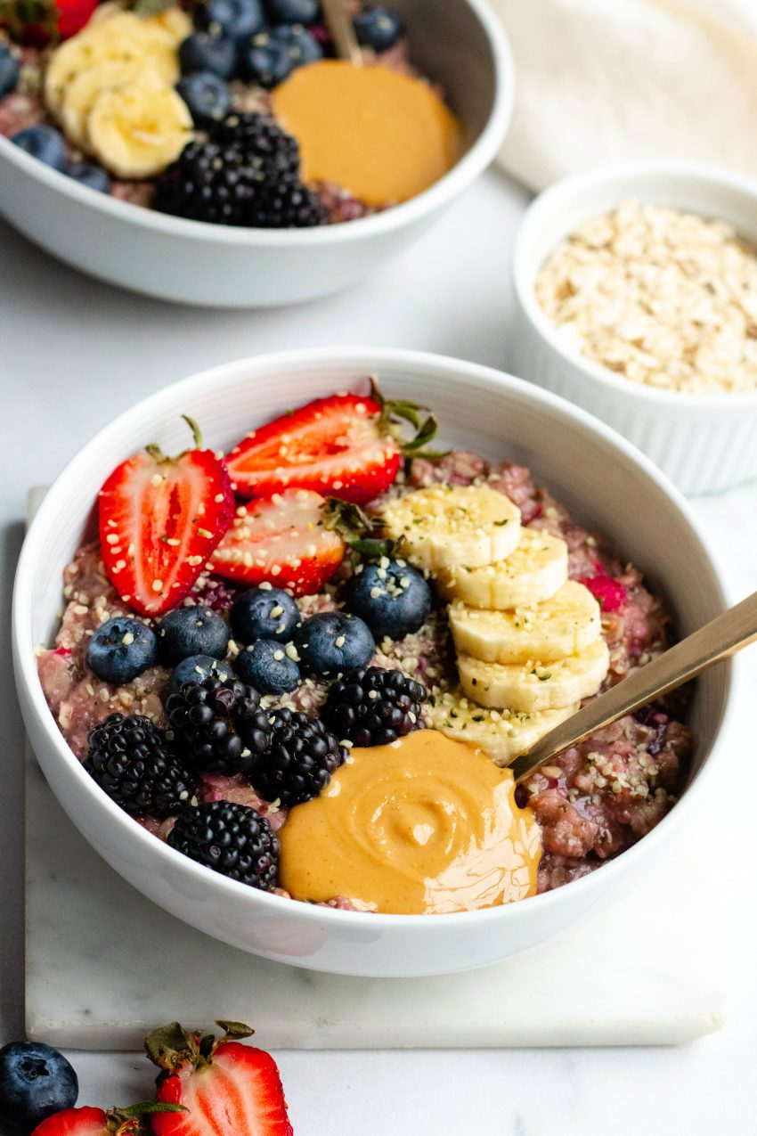 Two bowls of berry banana stovetop oatmeal with fresh berries, banana slices, and peanut butter