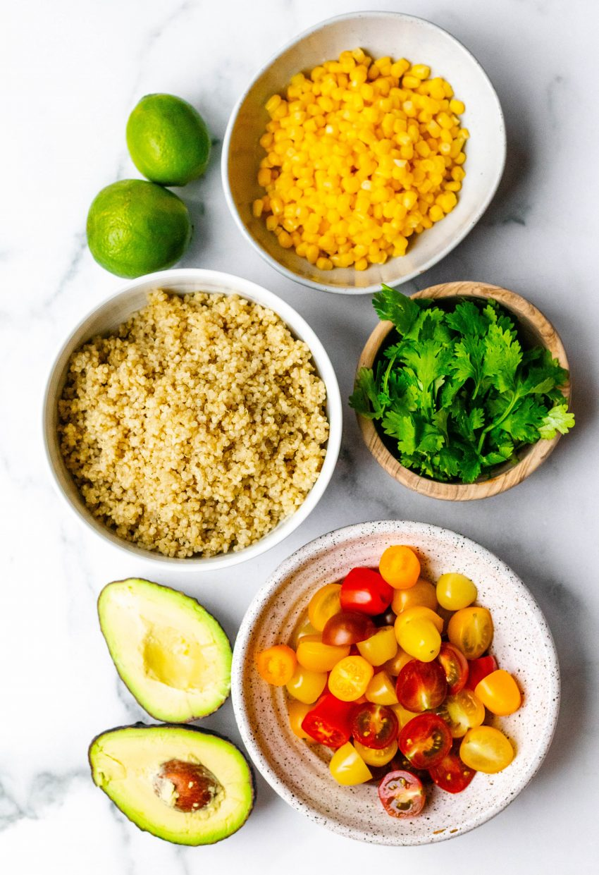 Cilantro lime quinoa salad ingredients in bowls on a white marble background
