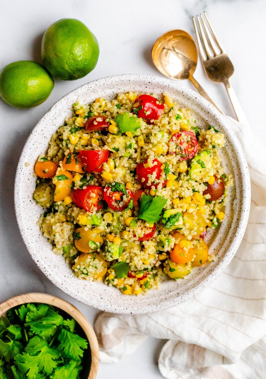 Cilantro lime quinoa salad with avocado in a bowl with ingredients around it and gold serving utensils