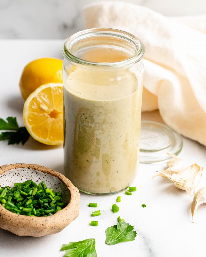 Healthy Tahini Goddess Dressing in a jar with ingredients around the jar