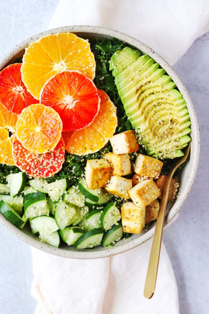 Kale salad with orange slices, cucumber, tofu, and avocado