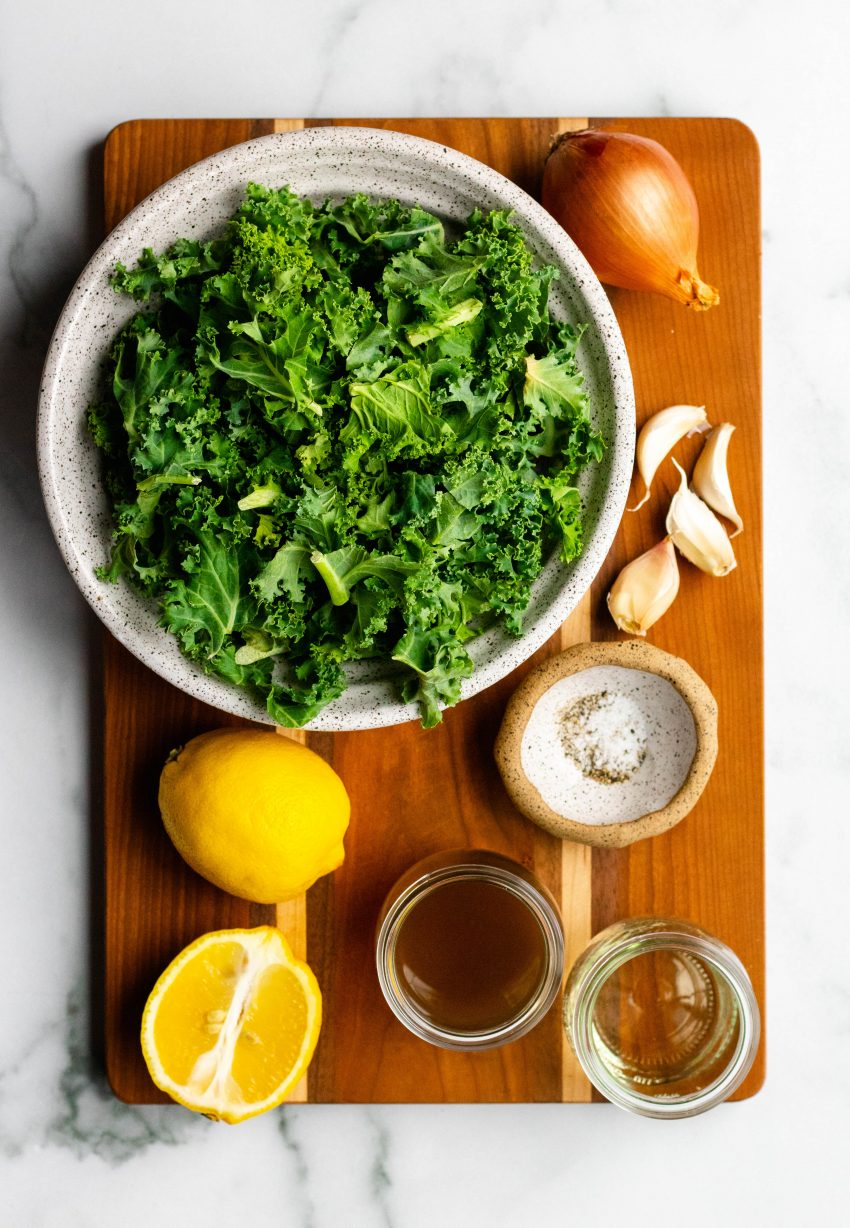 Lemon garlic braised kale ingredients in small bowls on a wooden cutting board