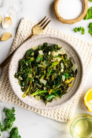 Lemon garlic braised kale in a speckled bowl with ingredients surrounding it