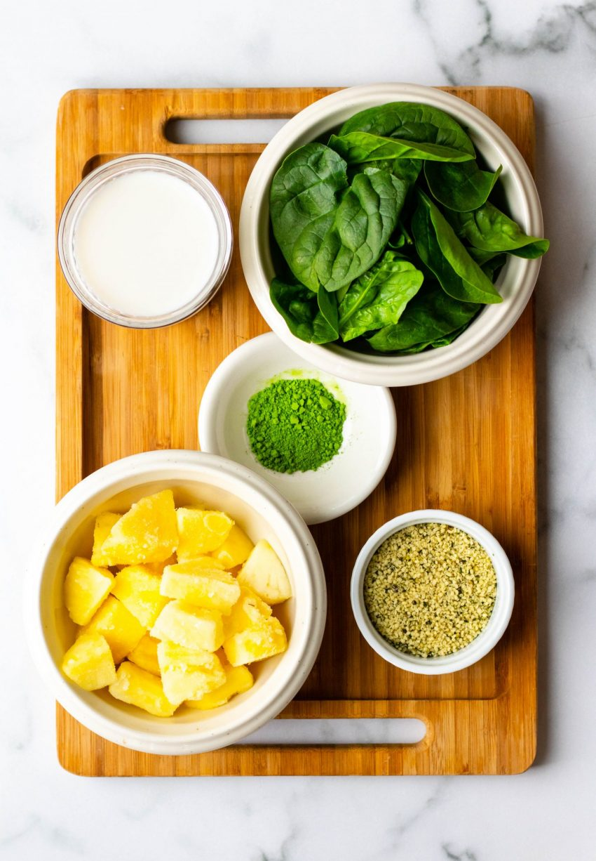 Pineapple matcha green smoothie ingredients in bowls on a wooden cutting board
