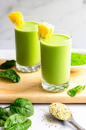 Two pineapple matcha green smoothies in glasses on wooden cutting board with ingredients surrounding the cups