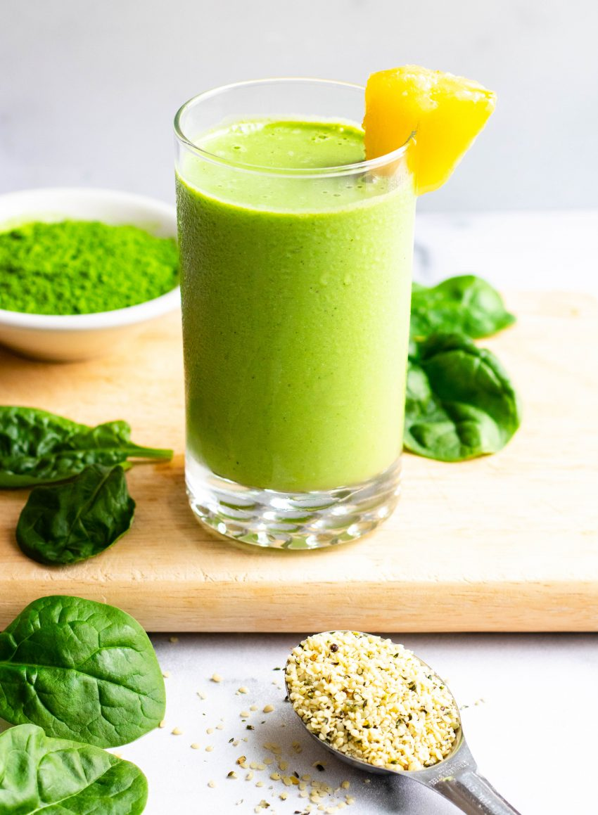 Pineapple matcha green smoothie in a glass on wooden cutting board with ingredients surrounding the cups
