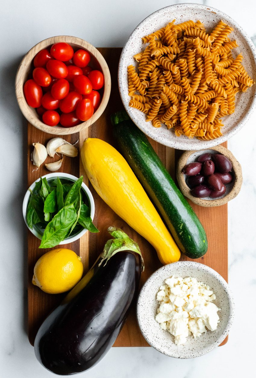 Roasted vegetable pasta salad ingredients on a wooden cutting board