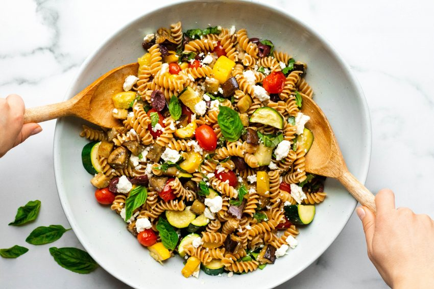 Two hands tossing pasta salad with wooden spoons