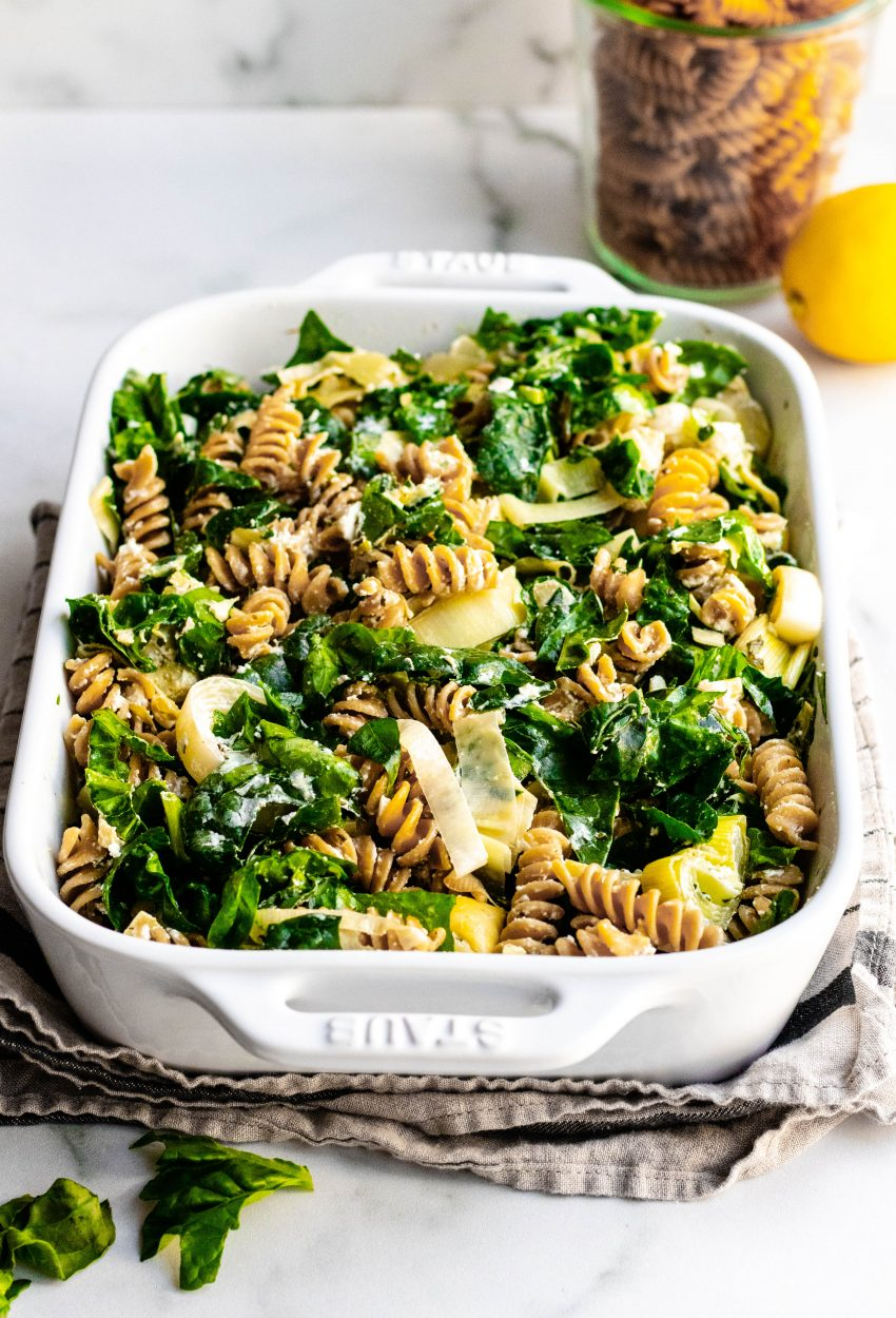 Baked Goat Cheese Spinach Artichoke Pasta in a rectangular white baking dish