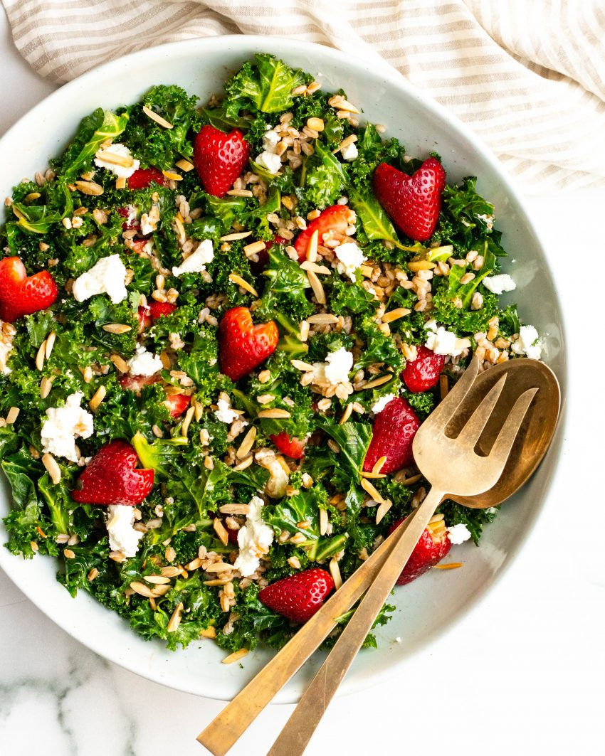Large bowl of strawberry kale salad with gold mixing utensils