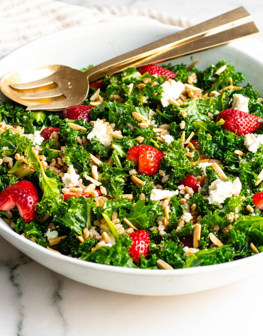 Strawberry Kale Salad in a bowl with brass serving spoons
