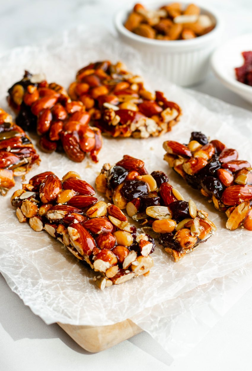Close up of 6 homemade honey nut KIND bars on wax paper