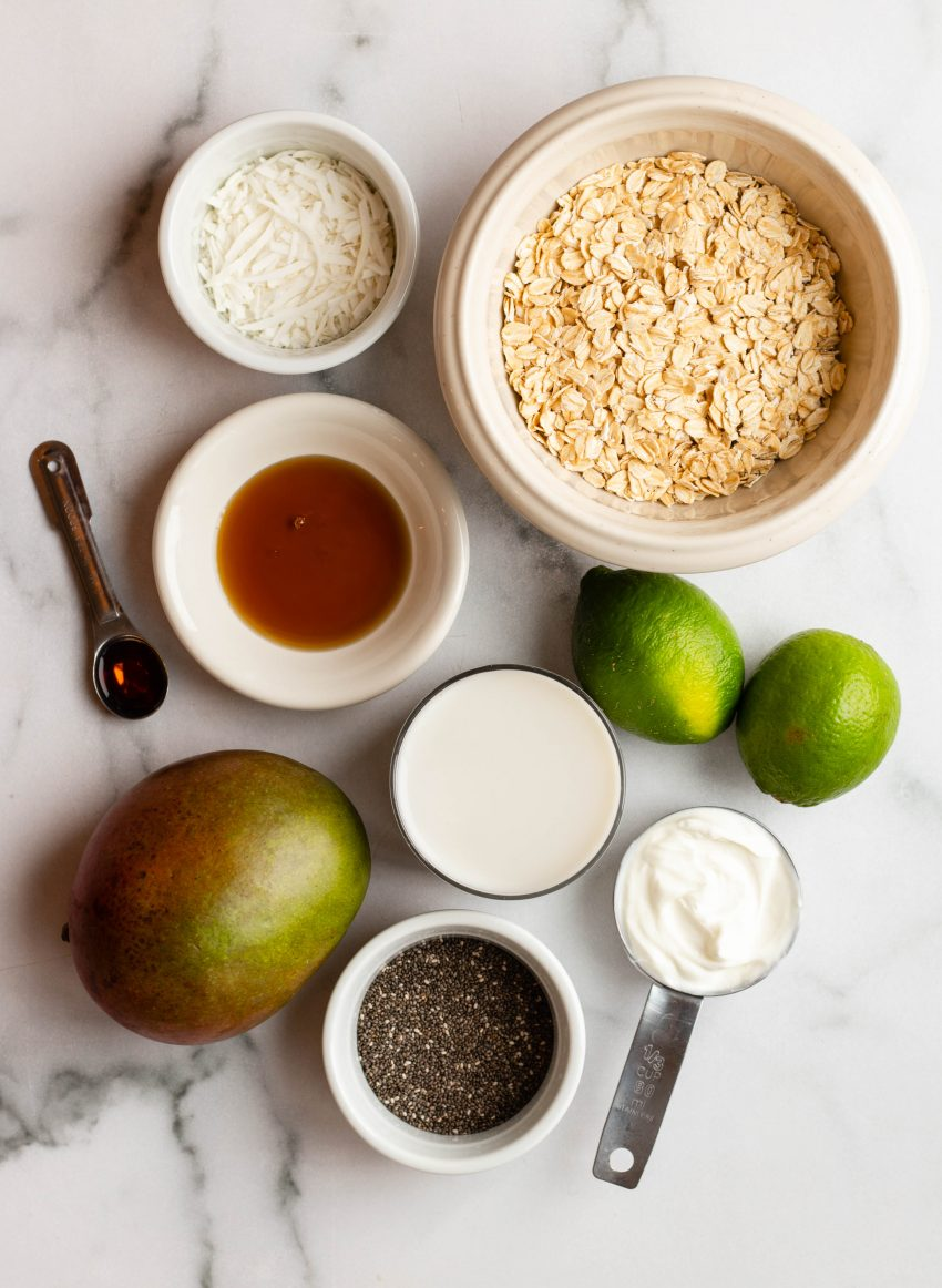 Mango lime overnight oats ingredients in bowls on a marble backdrop